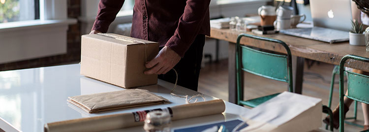 Small business owner packing a product
