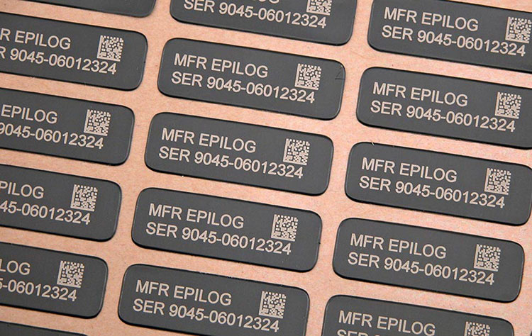 A jig of laser engraved anodized aluminum metal tags