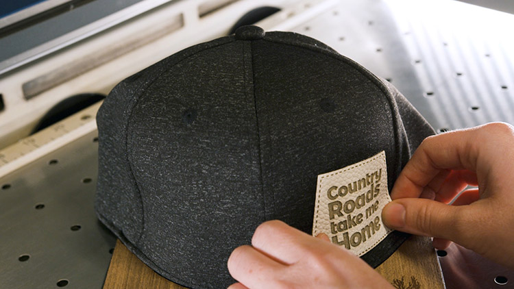 Applying the adhesive leather hat patch to the front of the cap.