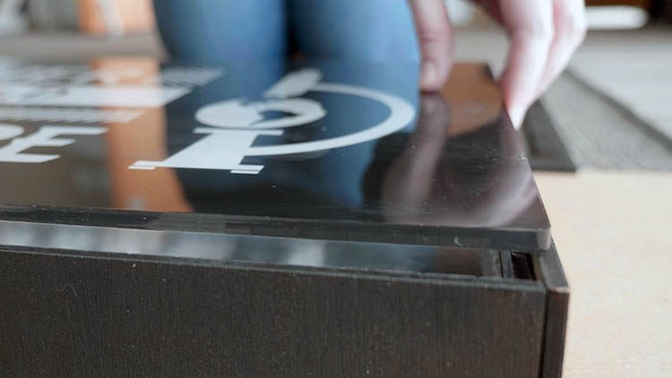 Close-up of inserting the acrylic into the front of the sign box.