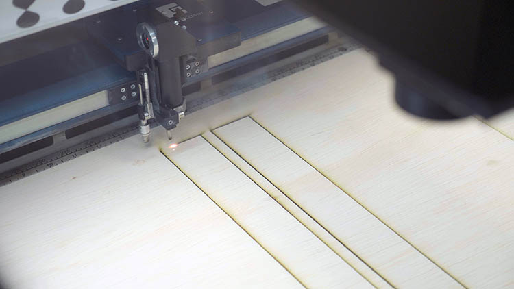 The Epilog Laser cutting out pieces of plywood.